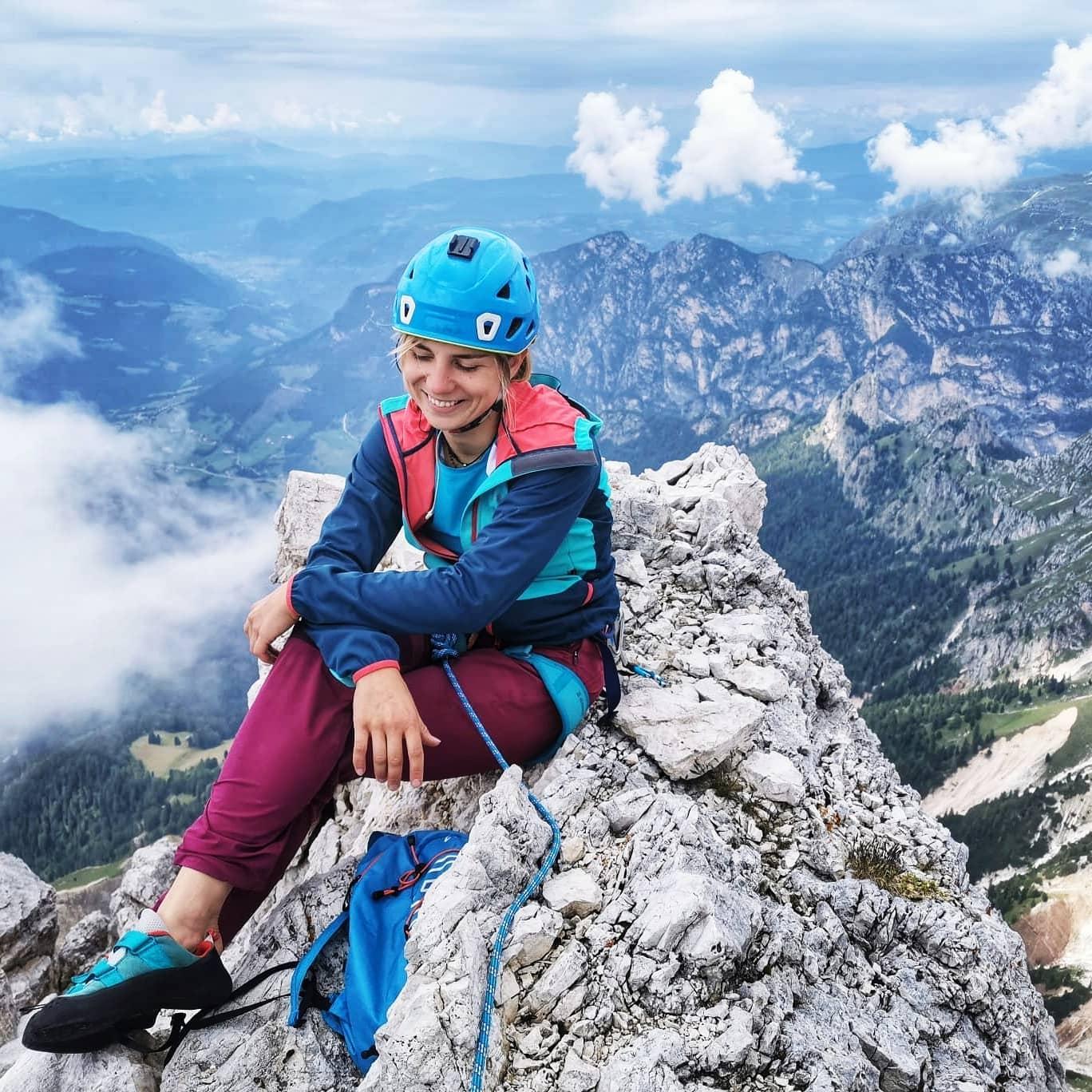Foto di una ragazza che sorride seduta sulla cima di una montagna
