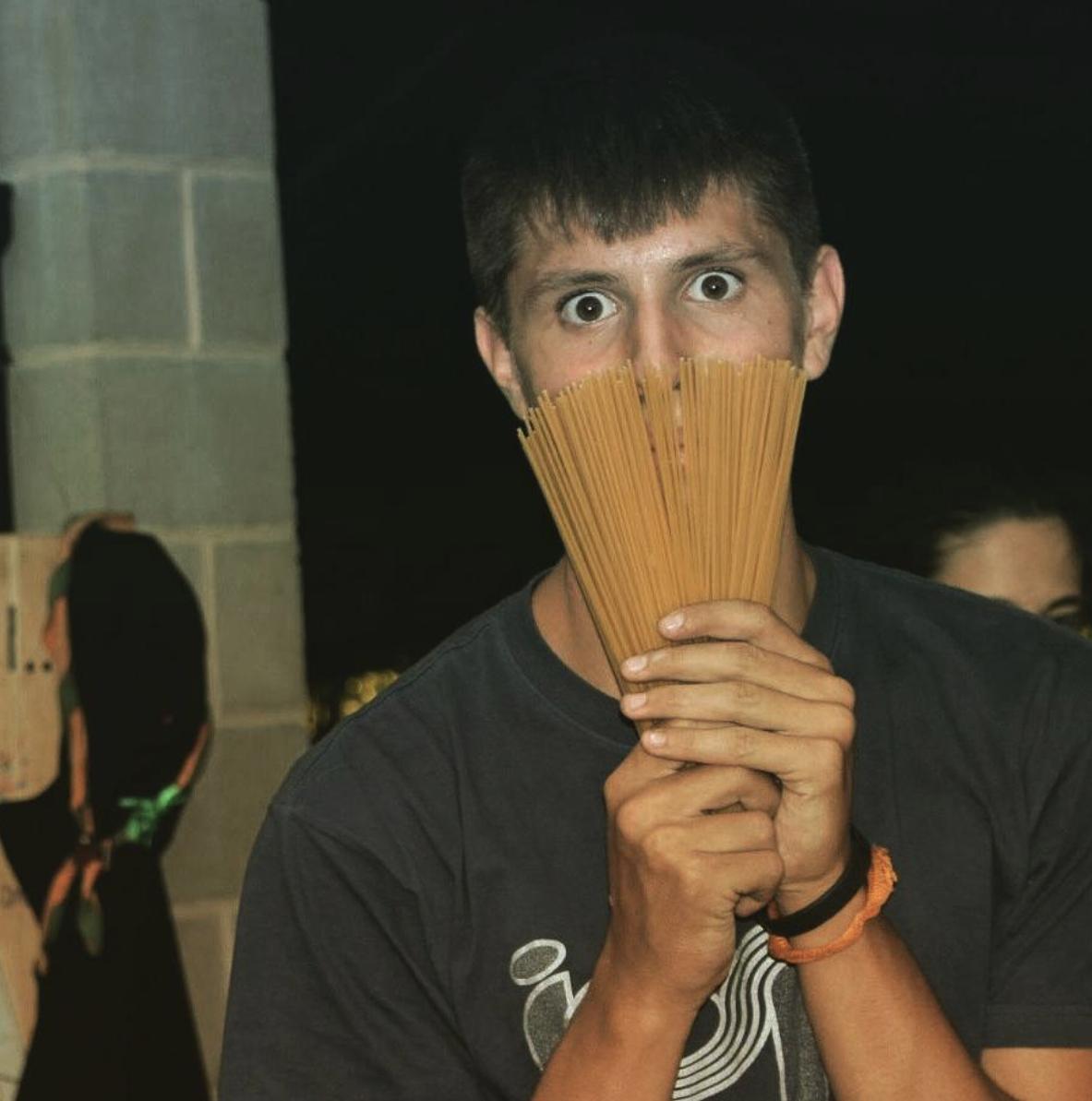 Foto di Matteo, amico di Davide con un'espressione divertente mentre si nasconde dietro agli spaghetti