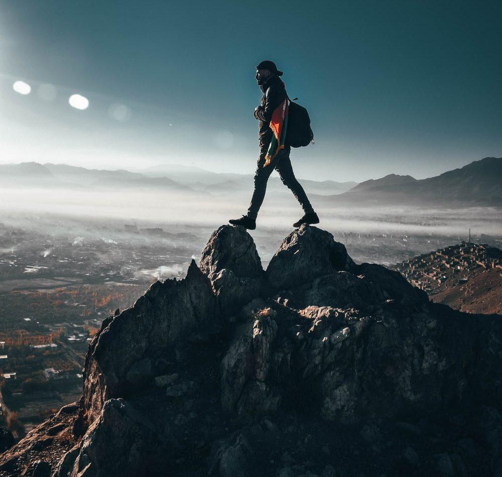 Foto di un ragazzo sulla punta di una montagna con un cielo sereni e soleggiato