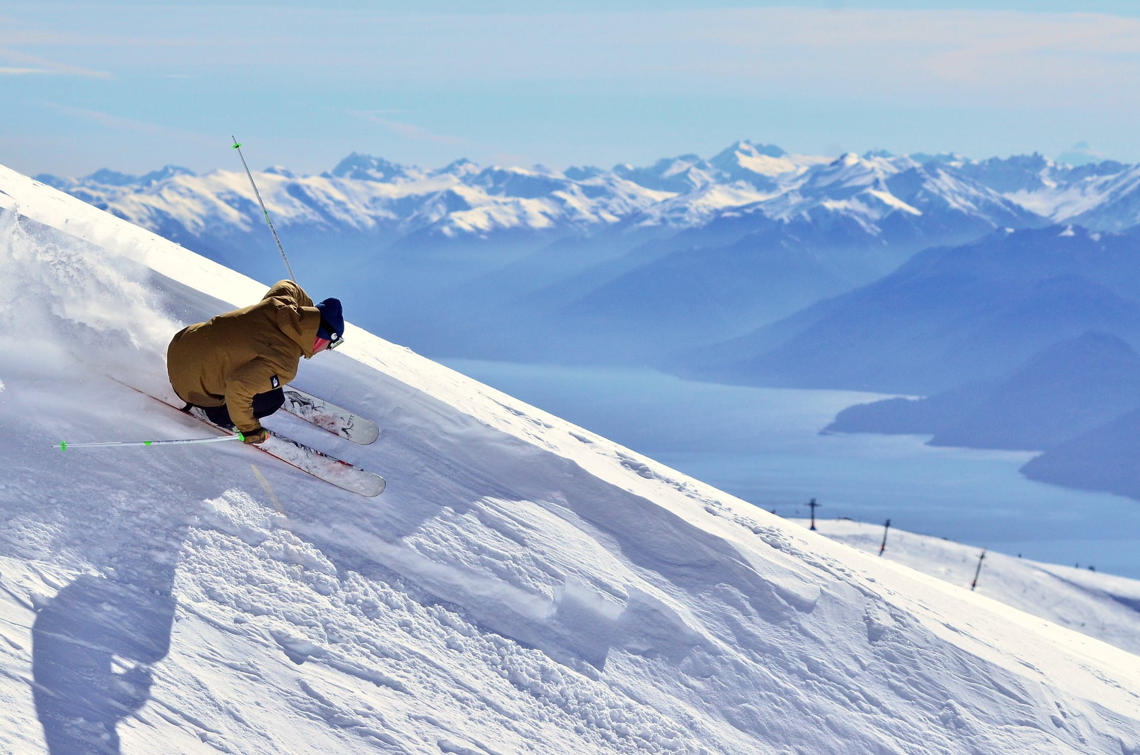 Foto di un ragazzo mentre sta sciando in una pista da scii su montagne coperte completamente di neve