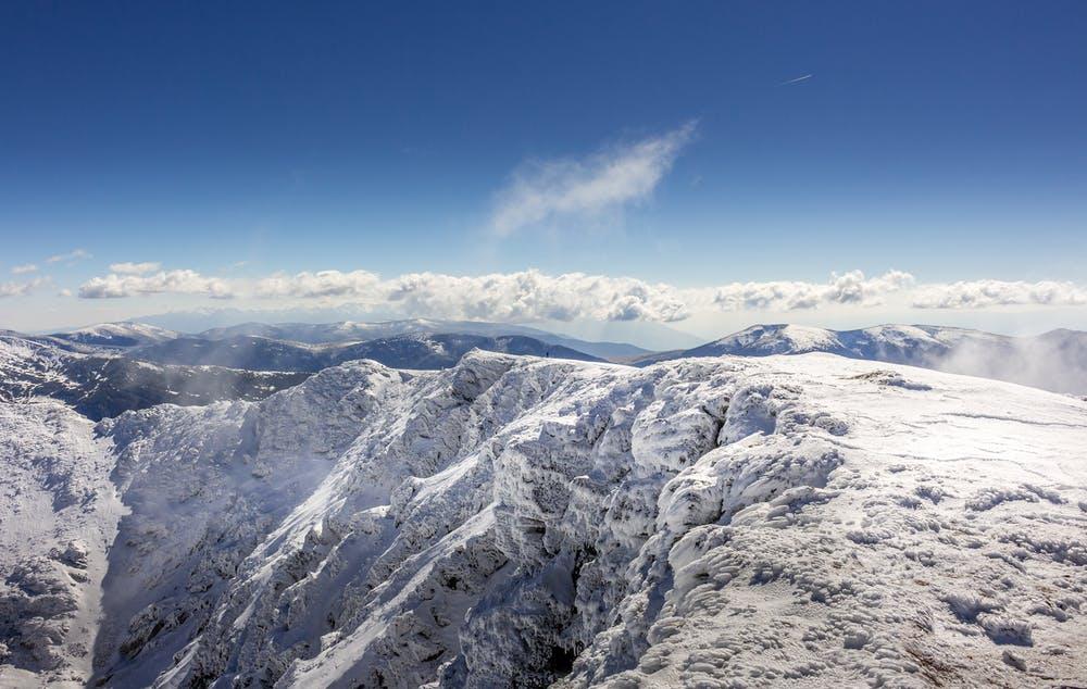 Vista dall'alto di montagne innevate con un cielo limpido