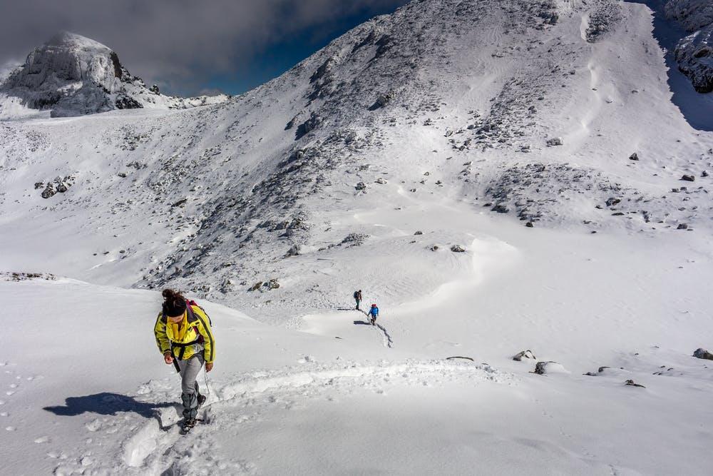 Vista di una grande montagna coperta di neve con dei ragazzi che stanno facendo un percorso verso un'altra montagna