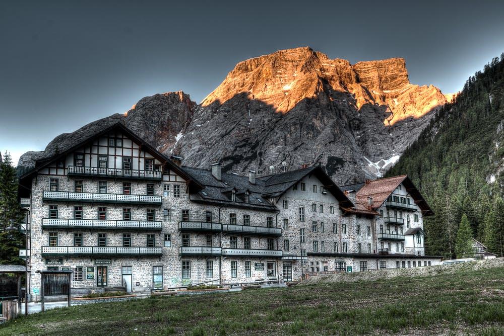 Vista di un grande rifugio con dietro delle montagne rocciose e illuminate dal sole