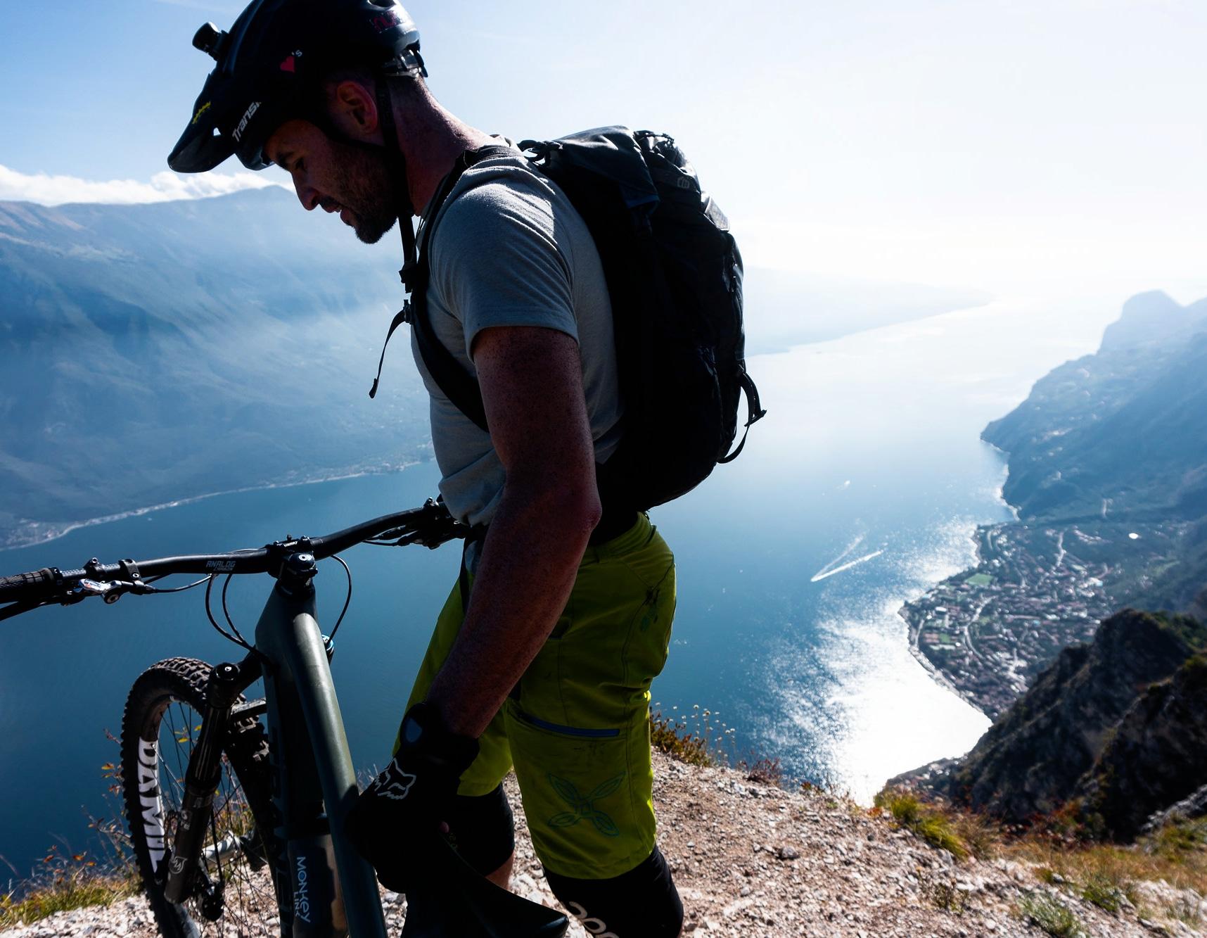 Foto di un ragazzo con la sua mountain bike con vista su un lago limpido