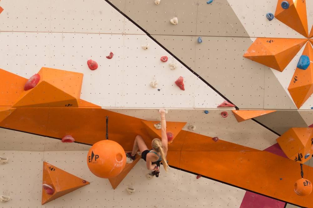 Foto di una ragazza mentre si sta arrampicando su un percorso costruito
