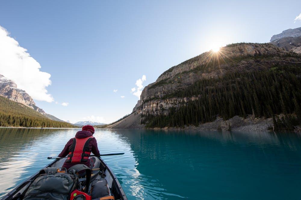 Vista lago lindo e alte montagne verdi e rocciose, in primo piano un ragazzo su una piccola barca