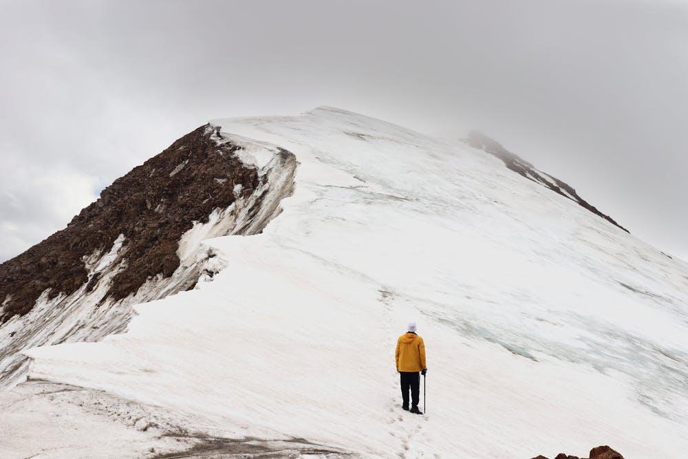 Vista della cima di una montagna innevata e un ragazzo vestito di giallo di spalle