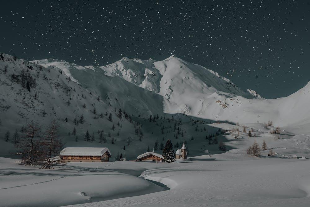 Vista montagne ricoperte di neve e dei rifugi con un cielo stellato