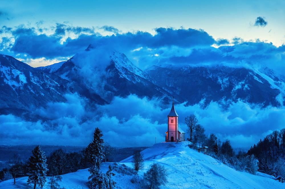 Vista montagne con neve e nubi sparse e in mezzo una chiesa illuminata da luce artificiale
