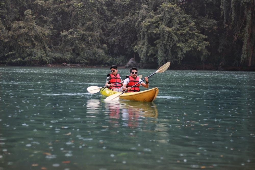 Foto di due ragazzi mentre fanno canoa in mezzo ad un lago circondato da alberi verdi