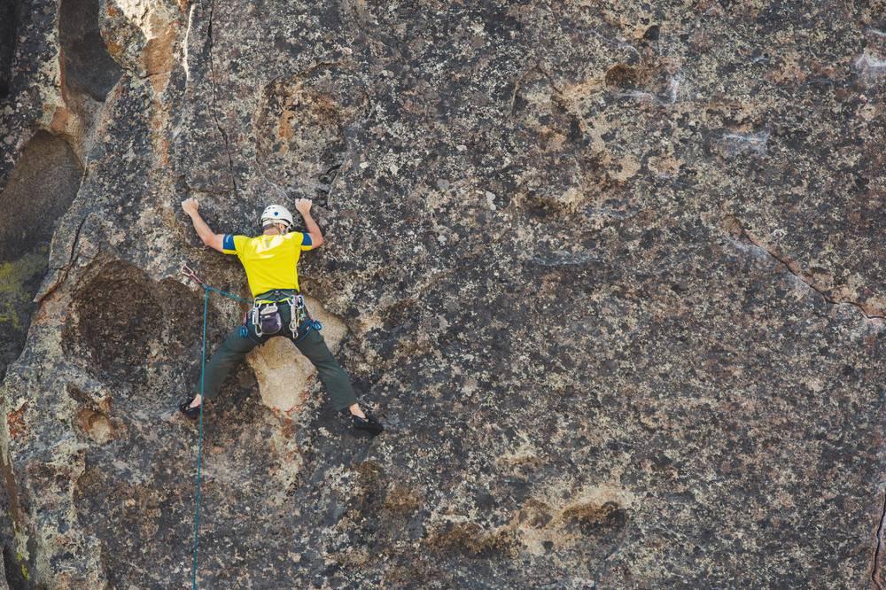 Foto di un ragazzo che i arrampica su una montagna