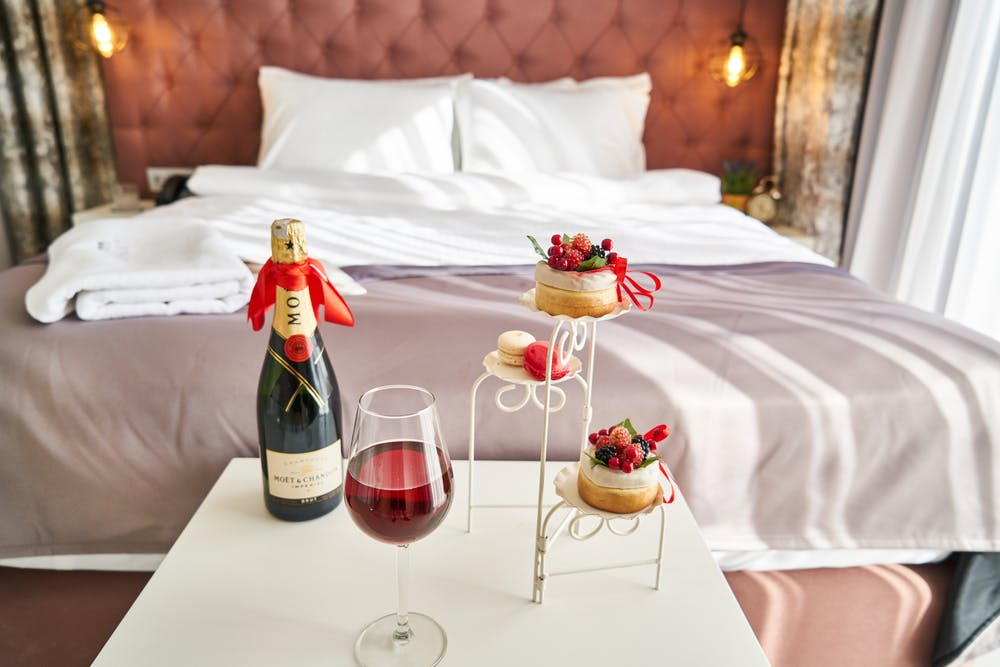Foto di una bottiglia di vino con il suo calice e dei dolci e dietro un letto matrimoniale