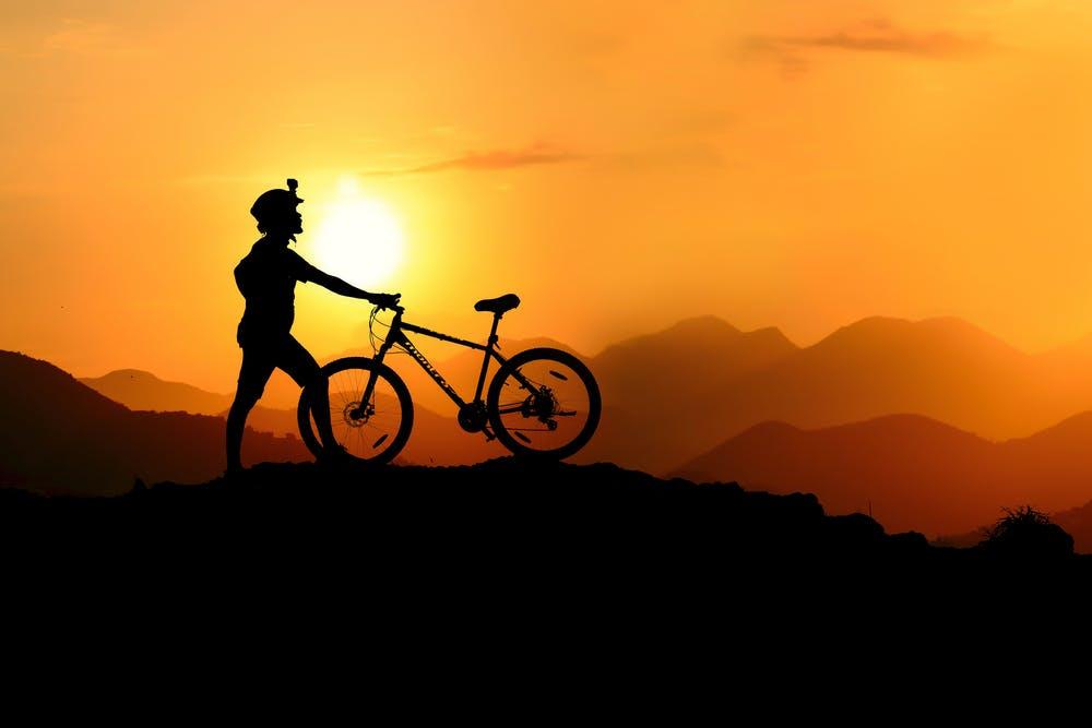 Vista tramonto delle montagne con un ragazzo e la sua bici