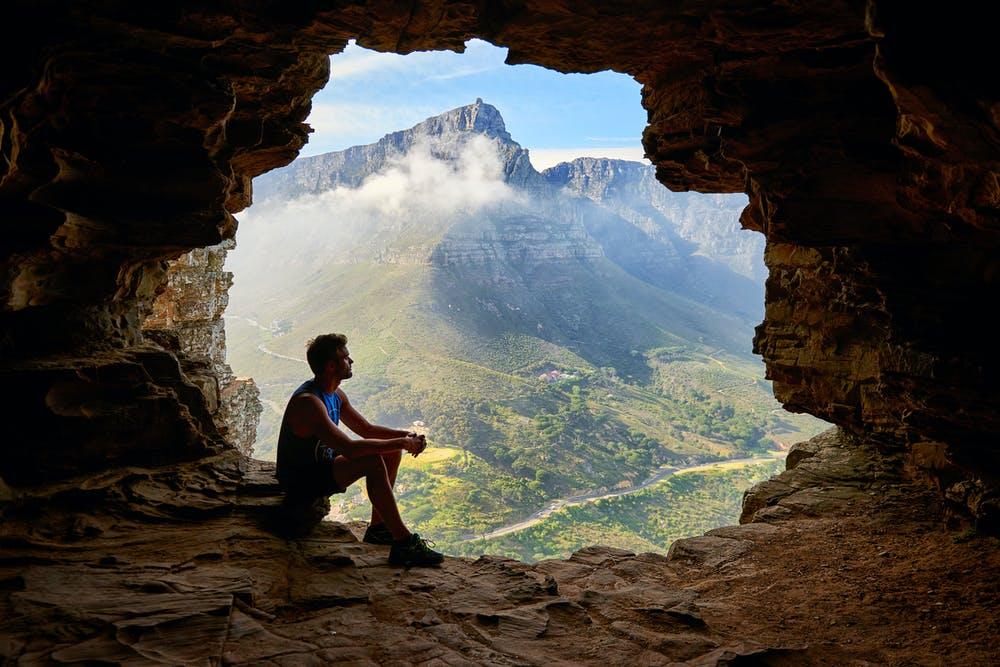 Foto di un ragazzo dentro una grotta con vista sulle montagne verdi