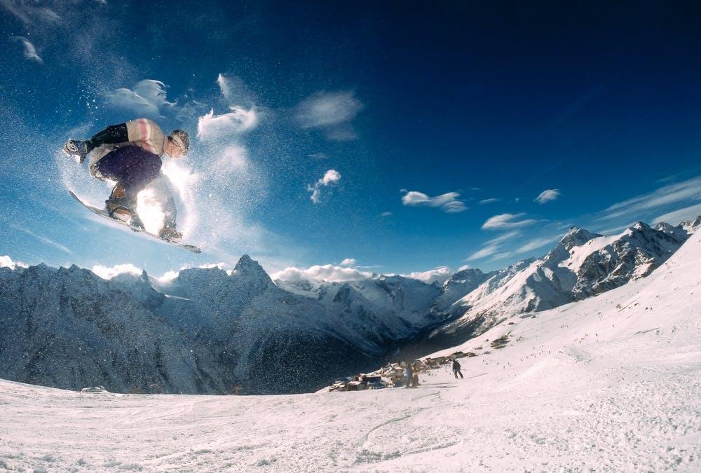 Vista montagne con la neve e una pista da scii con un ragazzo che fa snowboarding