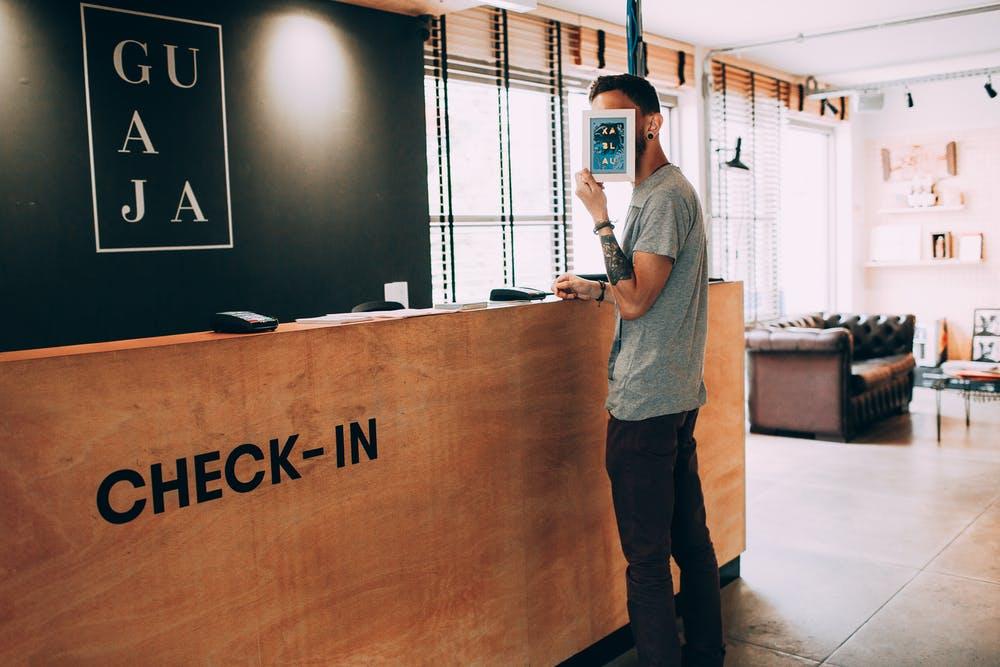 Foto di un ragazzo al check-in di un hotel mentre si copre il viso con un volantino