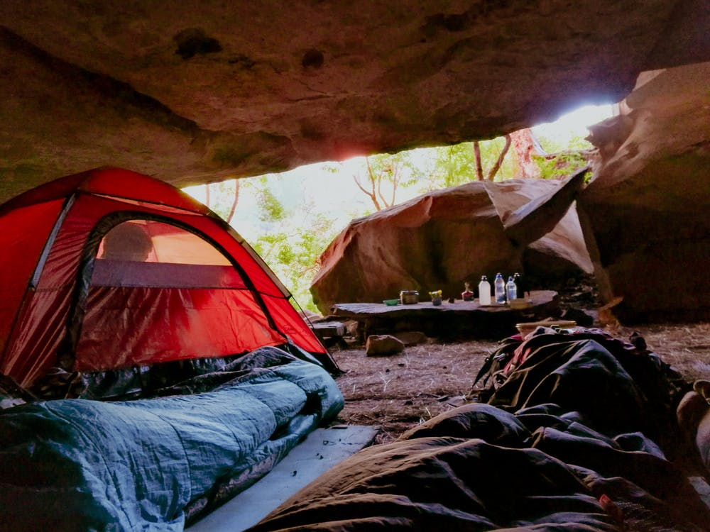 Foto di tende con all'interno delle persone dentro una grotta in montagna
