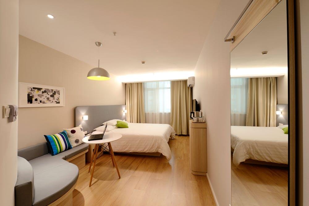 Foto di una camera di hotel con letto matrimoniale con un grande specchio