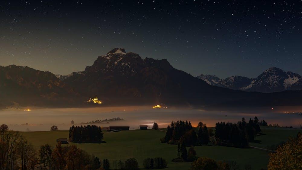 Vista notturna di alberi che contornano dei rifugi alpini e delle montagne