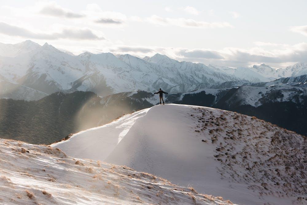 Vista di un ragazzo sulla cima di una montagna innevata in mezzo a alle montagne di neve