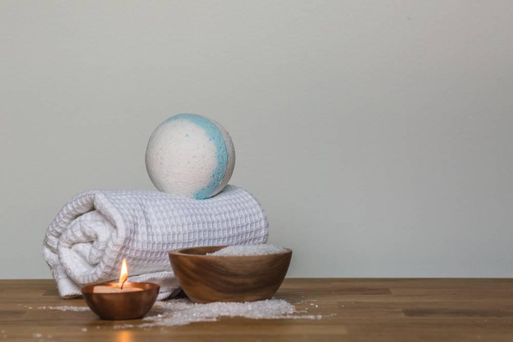 Foto di una salvietta bianca, una candelina e dei sali da bagno