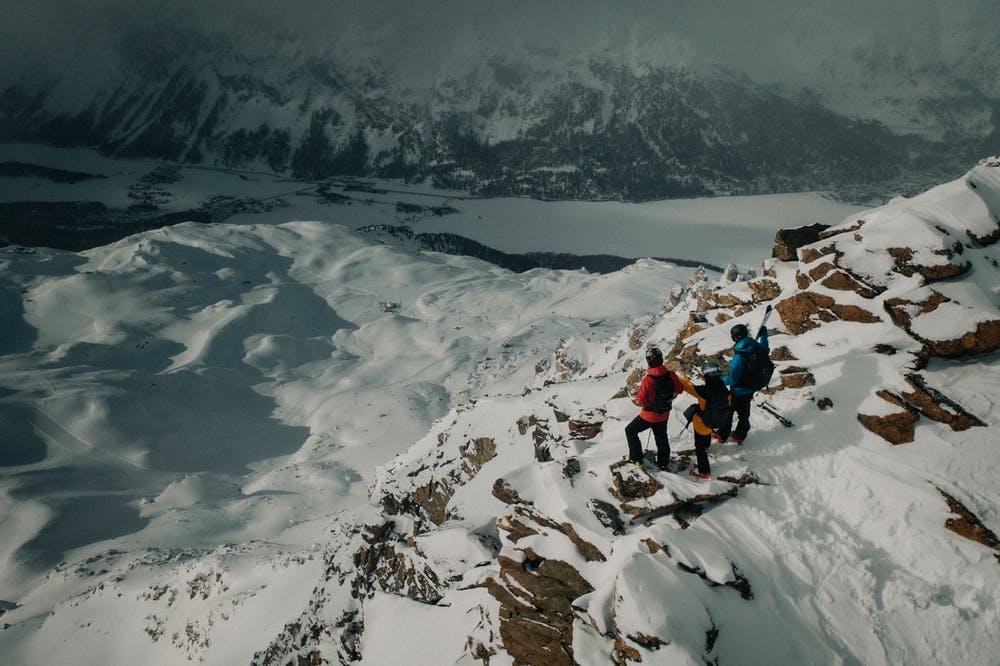 Vista montagne di neve e tre ragazzi fermi a contemplare il paesaggio