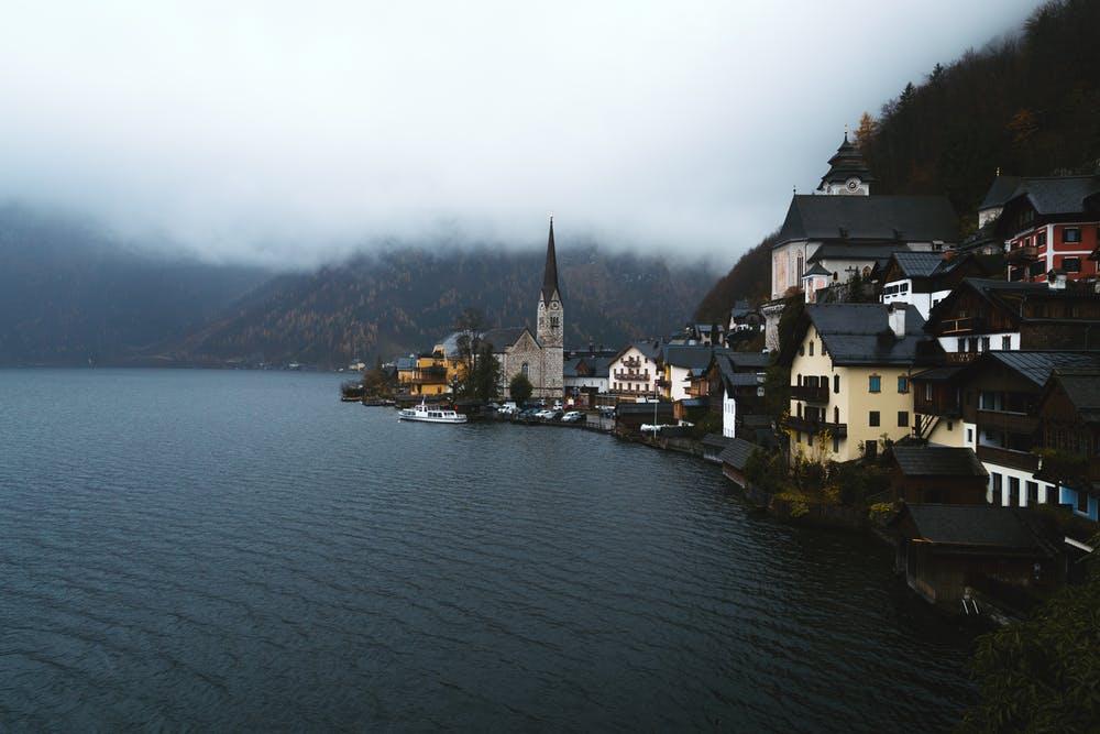 Vista abitazioni che si affacciano sul fiume e circondate da montagne con un cielo nuvoloso