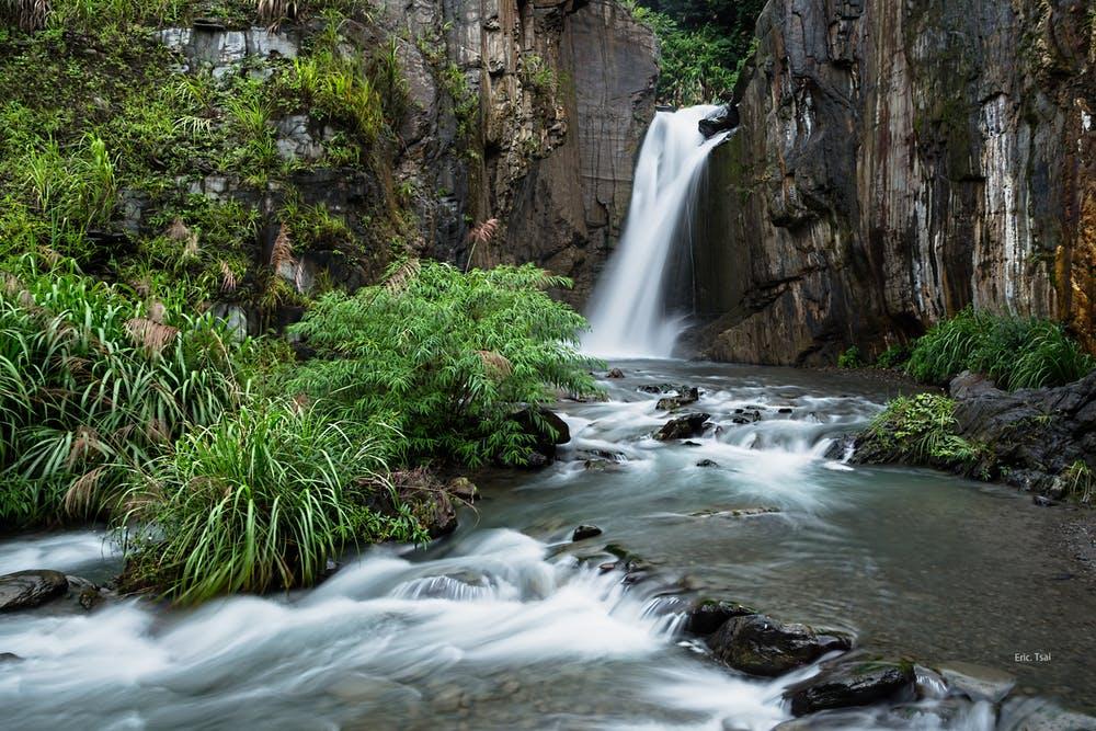 Vista cascata circondata da montagne e piante verdi