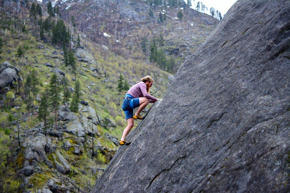 Foto di un ragazzo mentre si arrampica su una montagna