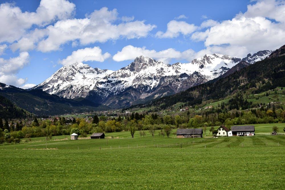 Vista montagne con neve che si affacciano su una collina verde con delle abitazioni
