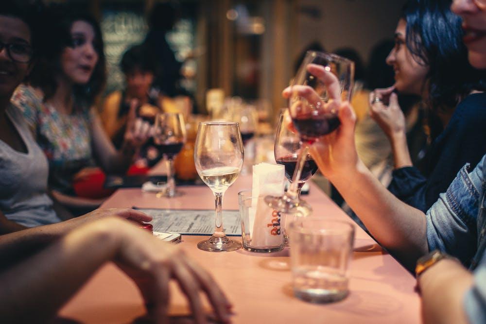 Foto di un gruppo di amici a tavola mentre chiacchierano