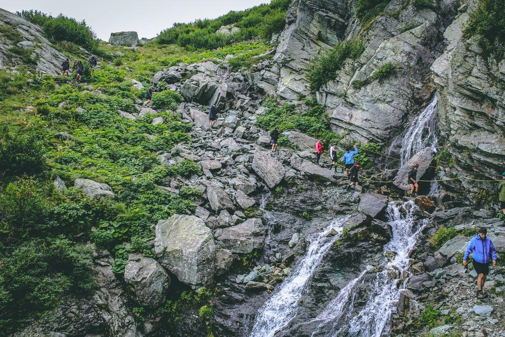 Vista di montagne verdi ed un percorso che stanno facendo dei ragazzi