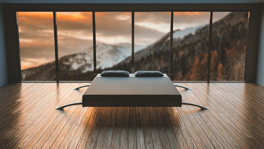 Vista letto matrimoniale con vetrate che si affacciano sulle montagne