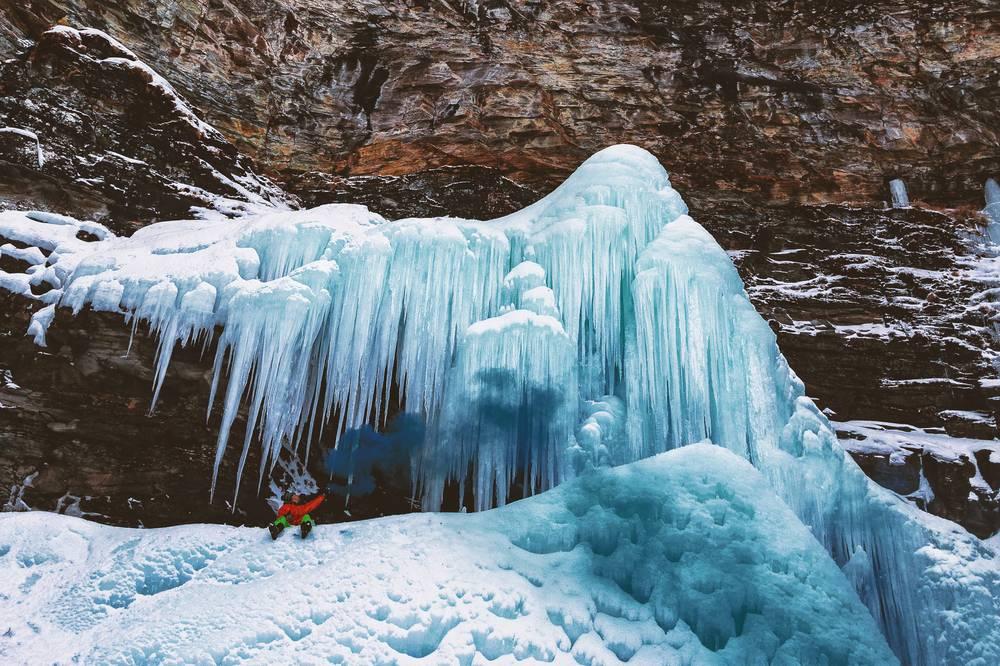 Vista montagna con chiazze di neve ed una cascata di neve ghiacciata con un ragazzo davanti