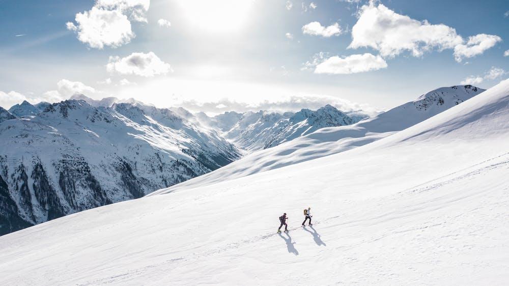 Vista montagne coperte di neve e due ragazzi che sciano