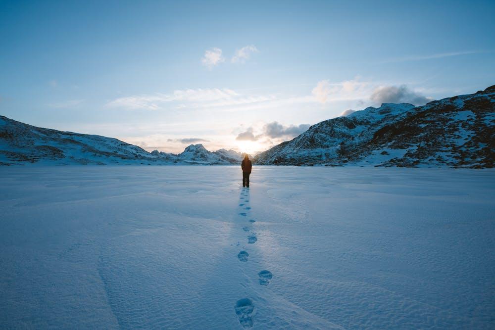 Vista lago ghiacciato con una persona in mezzo a delle montagne coperte di neve