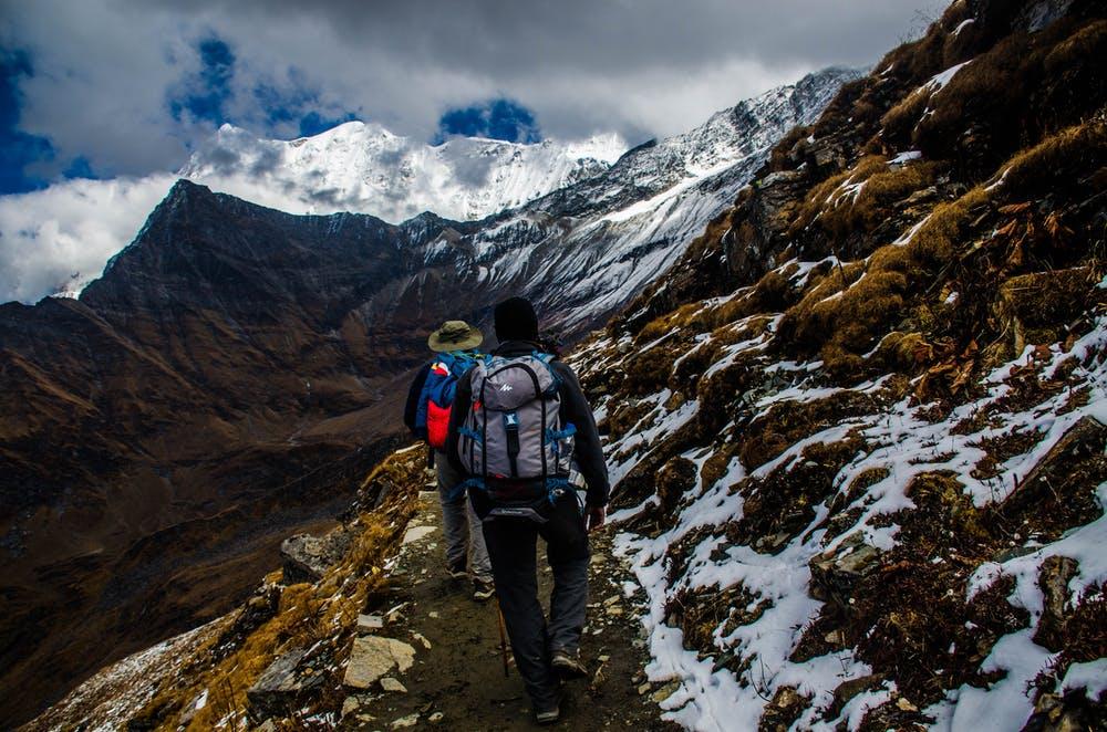 Foto di due ragazzi mentre fanno un percorso in montagna