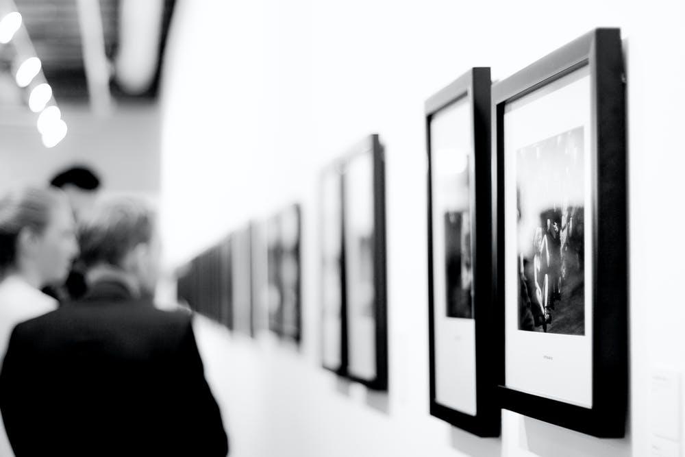 Foto di una serie di quadri e delle persone che li contemplano