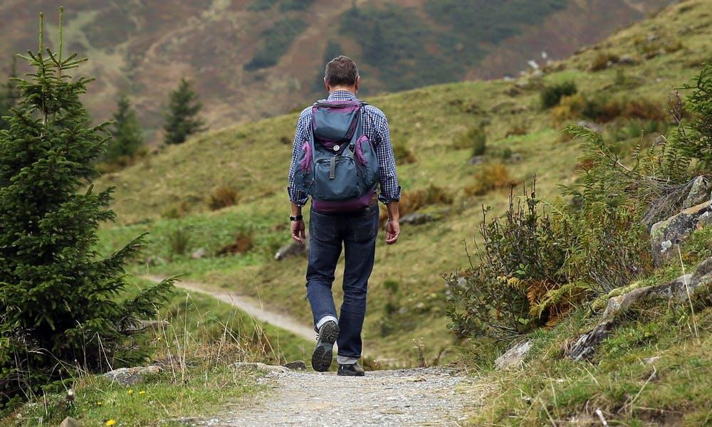Foto di un uomo mentre percorre un sentiero di montagna
