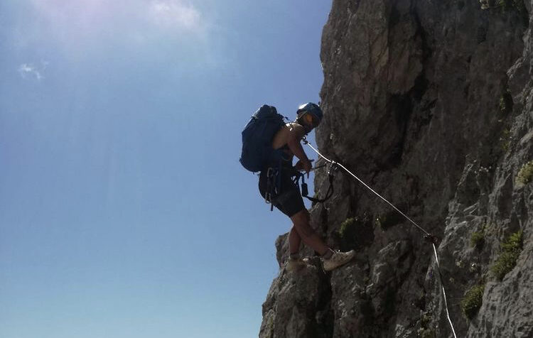 Foto di un ragazzo che si sta arrampicando su una montagna sotto un sole cocente