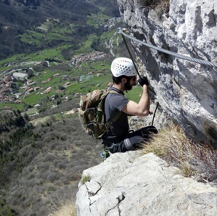 Vista dall'altro di un ragazzo che si arrampica sulla montagna e in sottofondo delle colline verdi contraddistinte da abitazioni sparse